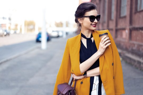 Portrait fashion woman in sunglasses walking on street . She wears yellow jacket, smiling to side.