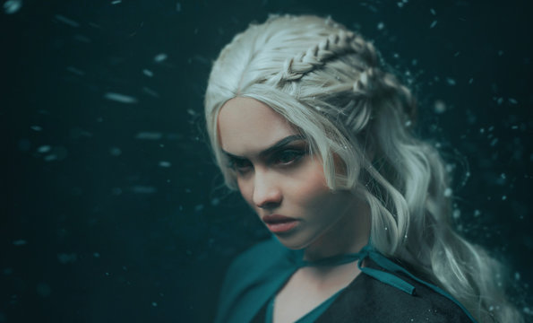 Portrait of a blonde girl close up. Background dark with flying snow, ash. White hair with creative braiding. Emotions of anger, and madness. The gothic queen on a deep winter night. Art photo
