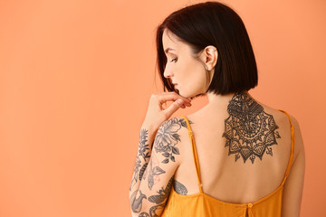Beautiful tattooed woman on color background