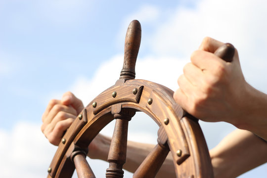 Steering hand wheel ship on sky background, hand hold hand wheel