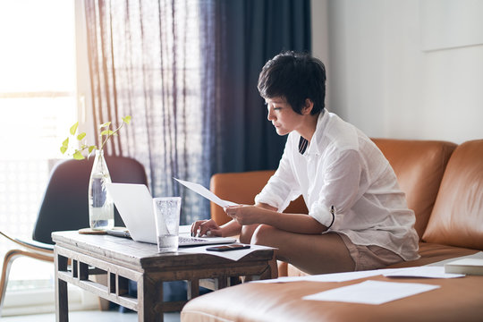 Asian businesswoman sitting on couch  & working on laptop at home