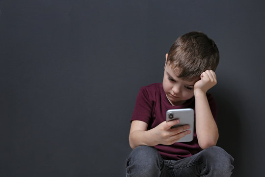 Sad little boy with mobile phone on black background, space for text
