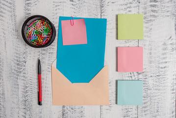 Envelope letter paper sticky note ballpoint clips holder wooden background