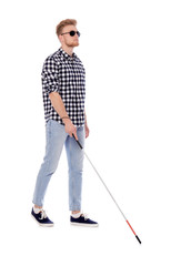 Young blind person with long cane walking on white background