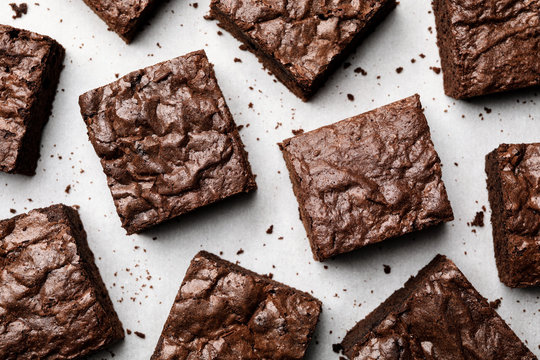 Flat lay composition with fresh brownies on parchment paper. Delicious chocolate pie