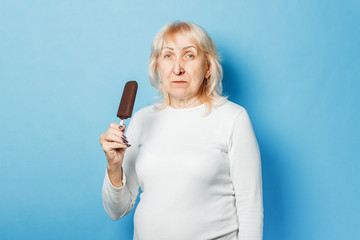 Old lady eating ice cream on a blue background. Concept summertime, summer, heat