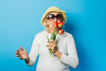 Old woman in a straw hat and sunglasses is holding a bouquet of tulips on a blue background. Concept of the onset of spring, summer time, vacation, camping