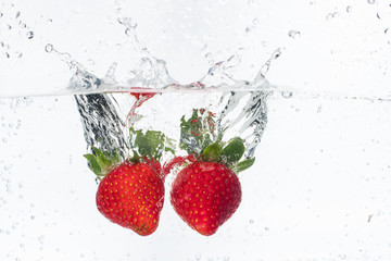 Papiers peints Dans la glace ripe red strawberries are thrown and dropped into sparkling water, many bubbles