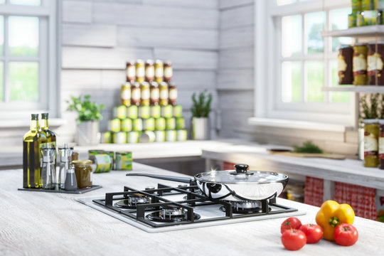 A new gas cooker and a shiny chrome-plated frying pan in a rustic wooden interior with large windows. Around cans with preserves and spices