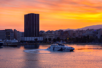 Piraeus Port, Attica / Greece. Colorful sunrise with fiery sky over the port and the city of Piraeus. Seajets vessel is making manoeuvring at the port