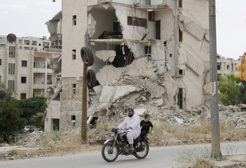 A man rides on a motorbike past rubble of damaged buildings in the city of Idlib