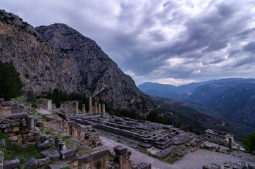 Delphi, Phocis / Greece. Temple of Apollo at the archaeological site of Delphi visible today date from the 4th century BC, and are of a peripteral Doric building. Panoramic view, cloudy sky