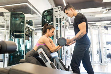 Trainer Helping His Client To Achieve Her Goal