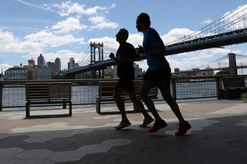 People are seen in silhouette running underneath the FDR drive near the Manhattan Bridge in New York City