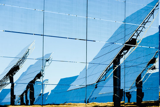 Reflection of modern solar panels on glass wall during sunny day in photovoltaic power station in countryside
