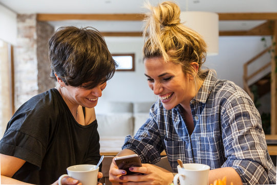 Two beautiful and young women having breakfast at home and having fun, using the smartphone