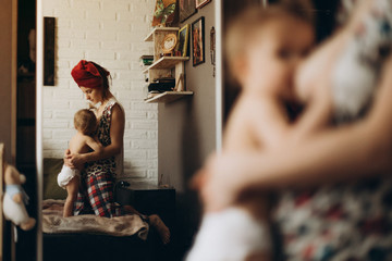 weekdays young mother who feeds her daughter feeding in their bedroom photos from the reflection in the mirror.