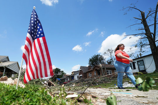A woman looks for her cat in a destroyed neighborhood following a tornado in Jefferson City