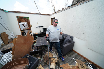 A man works to remove valuables from a home in a destroyed neighborhood following a tornado in Jefferson City