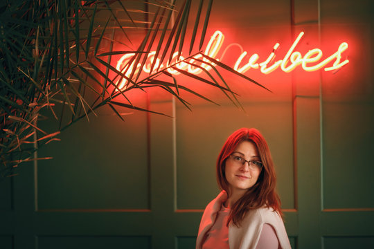 Smiling young woman under the neon sign of a cafe