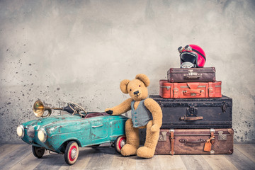 Teddy Bear toy standing near rusty retro  pedal car from 60s, antique travel trunks luggage, old leather valises, red helmet with outdated goggles front loft background. Vintage style filtered photo