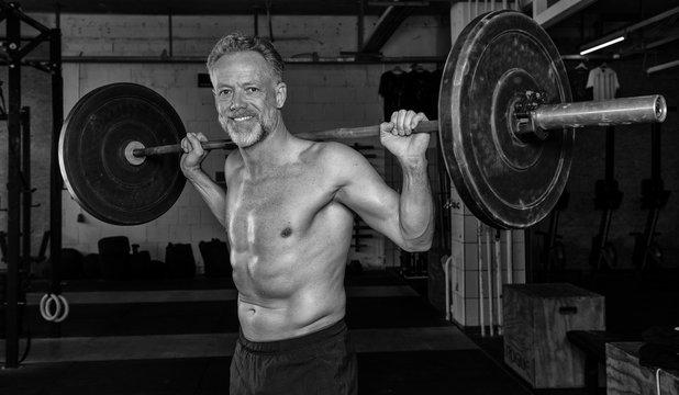 Ein durchtrainierter Mann mittleren Alters macht oberkörperfrei die Übung Clean und Jerk. Fitnesstraining mit der Langhantel. Training mit Gewichten.  Schwarz-weiß Porträt.