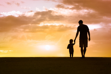 Silhouette of loving father walking side by side with son holding hands.