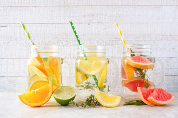 Variety of citrus infused detox water drinks in mason jar glasses against a white wood background