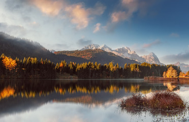 Foto auf Gartenposter Reflexion fantastic foggy landscape at Germanian Alps. Colrful Clouds on the Blue Sky over the Zugspitze mountains at early morning in autumn, Bavaria, Germany. Fresh grass on foreground.