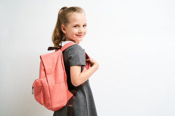 Little girl photographed against white background wearing school uniform dress isolated holding a coral backpack on both shoulders Wall mural