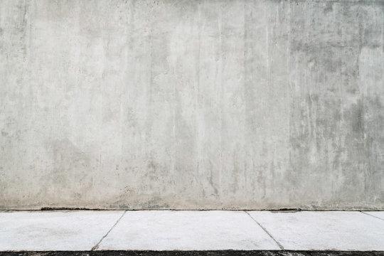 Empty grunge wall with a white sidewalk.