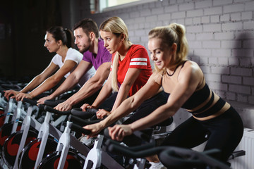 Group of smiling friends at gym exercising on stationary bike. Happy cheerful athletes training on...