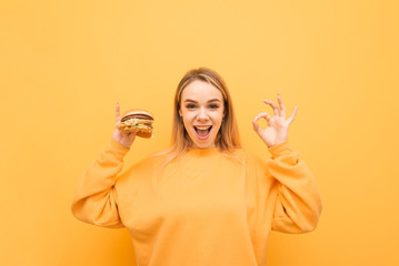 Joyful girl with a burger in her hand stands on a yellow background, shows an OK sign and looks at the camera and smiles. Expressive happy girl with fast food in hand.
