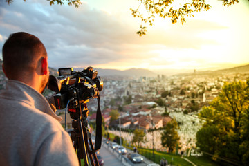 video camera, cameraman, sunset. The photographer records the sunset in the background of a beautiful city
