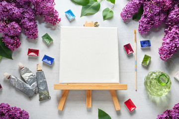 Watercolor paints, brush for painting, paint tubes, empty canvas on easel, watercolor paints and lilac flowers.