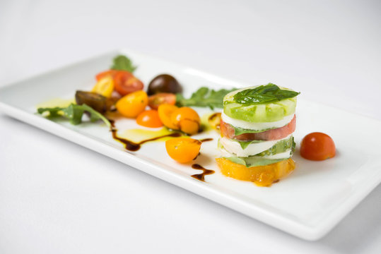 Caprese salad on a white square plate