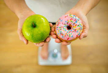 Woman on scale measuring weight holding apple and donuts choosing between healthy or unhealthy food