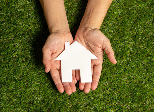 Hands holding a house in conceptual image of plans for housing investment and property business