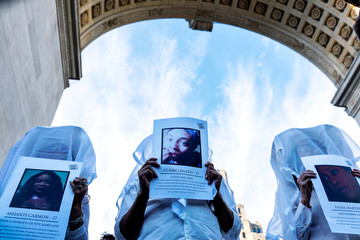 Transgender rights activists hold pictures of transgender women who were killed this year as they protest the recent killings of three transgender women, Muhlaysia Booker, Claire Legato, and Michelle Washington, during a rally at Washington Square Park