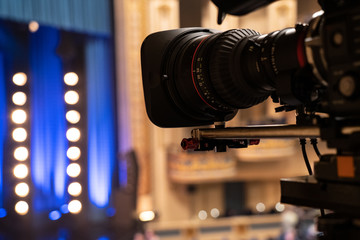 Film camera shooting a performance in a theater with blurred stage lights in the background