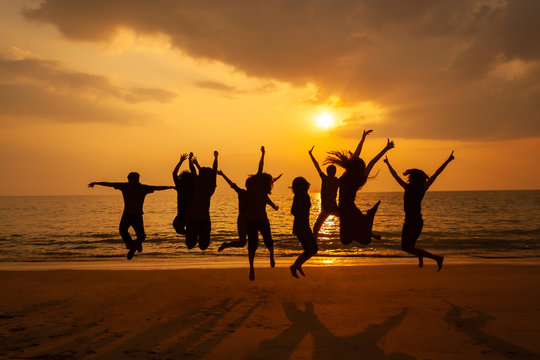 Silhouette photo of the team celebration on the beach at sunset