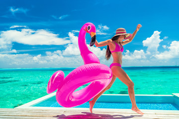 Vacation fun woman in bikini with funny inflatable pink flamingo pool float running of joy jumping by infinity swimming pool. Girl enjoying travel holidays at resort luxury overwater bungalow travel.