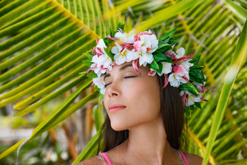 Exotic beauty wellness woman relaxing with closed eyes on tropical beach with Tahiti wreath of flowers hair accessory. Bora Bora, French Polynesia.
