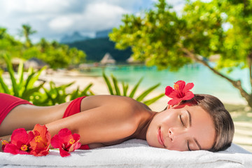 Woman relaxing at spa luxury massage hotel resort. Beauty girl lying down sleeping on towel with hibicus flowers outside. Serene ethnic woman relaxing. Mixed race Asian / Caucasian model outdoor.