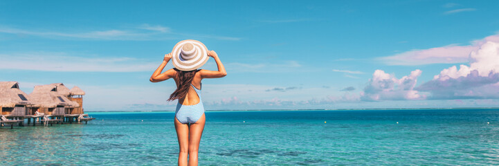 Wall Mural - Beach summer travel vacation banner panorama woman in swimsuit and hat over blue ocean sky copy space with overwater bungalows hotels in the background.