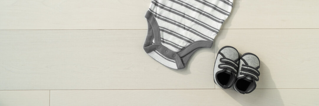 Baby clothing shoes and onesie bodysuit layed flat on wood background banner panorama with copy space for newborn clothes advert concept.