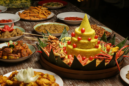 Nasi Tumpeng. Yellow rice in a cone shape. A festive Indonesian rice dish with side dishes.