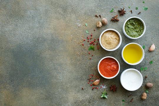 Set of sauces on gray background. Marinara or tomato sauce, yogurt, pesto, olive oil and mustard