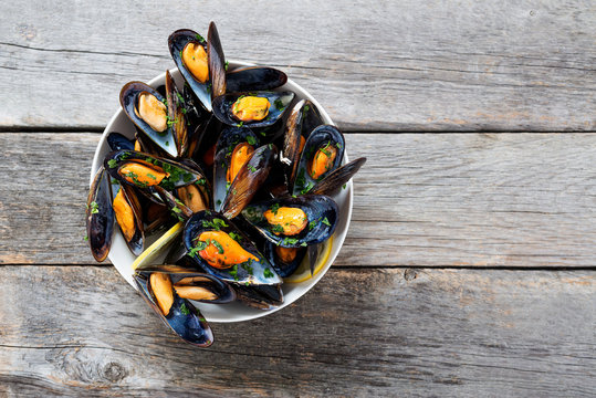 Delicious seafood mussels with  parsley sauce and lemon.
