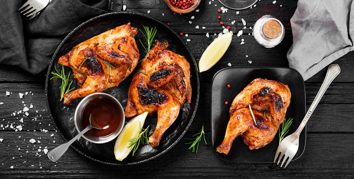Halves of appetizing grilled juicy chicken with golden brown crust served with lemon slices,barbeque  sauce and rosemary.